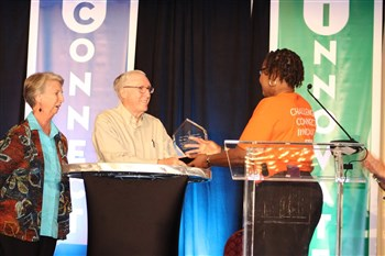 Martha Gay Duncan, left, watches husband Mont Duncan receive church planters award from Candace Lewis